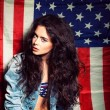 Beautiful sexy long haired girl against american flag — Photo