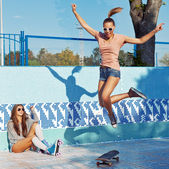 Two beautiful young girls in sunglasses in an empty pool — Stock Photo