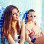 Two beautiful young girls on the floor of an empty pool — Stock Photo