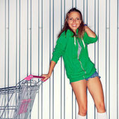 A beautiful young girl in roller skates near supermarket trolley — Stock Photo