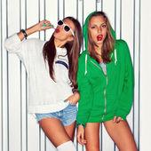 Dvě krásné mladé dívky s červenými lízátka u zdi — Stock fotografie