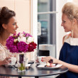 Two beautiful young girls in summer outfit sitting at the table — Stock Photo