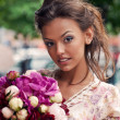 A beautiful young girl in summer dress with a bunch of flowers i — Stock Photo #44084825