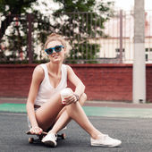 Beautiful sexy lady in jeans shorts with skateboard and to-go cu — Stock Photo
