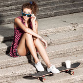 Beautiful sexy lady in jeans shorts with skateboard at stone sta — Stock Photo
