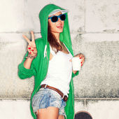 Beautiful sexy lady in jeans shorts with skateboard against  gre — Stock Photo