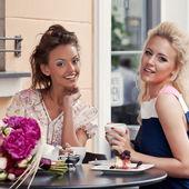 Dvě krásné mladé dívky v letním oblečení mají oběd na kartě — Stock fotografie