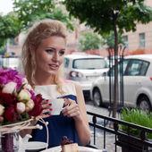 Krásná mladá blondýnka v létě šaty u stolu v pav — Stock fotografie