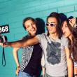 Young people having fun in front of light blue brick wall — Stock Photo #44093831