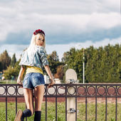 Blonde girl in short denim shorts with roses wreath on head — Stock Photo