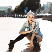 Beautiful blonde girl in short shorts with skateboard — Stock Photo