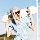 Beautiful blonde girl in short shorts with skateboard — Stock Photo