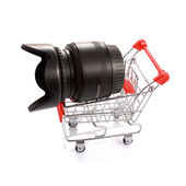 Camera lens with hood in shopping cart isolated on white — Stock Photo