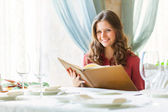 A woman in a restaurant with the menu in hands — Stock Photo