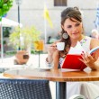 Stock Photo: Young woman is sitting in the cafe