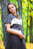 Young woman is standing near the tree — Stock Photo