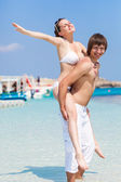 Young couple is having fun on the beach — Stock Photo