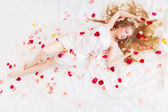Beautiful girl is relaxing in rose petals — Stock Photo