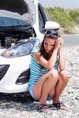Junge Frau sitzt auf der Straße in der Nähe des Autos — Stockfoto