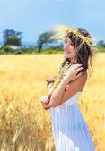 En kvinna är i fältet med en krans — Stockfoto