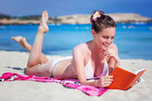 Woman is reading a book on a beach — Stock Photo