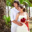 Stock Photo: Bride and groom near palm-tree