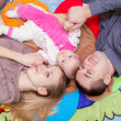 Family are lying on the floor with their baby — Стоковое фото