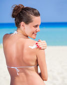 A woman is applying sunblock — Stock Photo