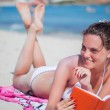 Woman is reading a book on a beach — Stock Photo #45985081
