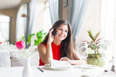 Woman in restaurant is talking to mobile phone — Stock Photo