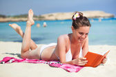 女人读一本书的沙滩上 — 图库照片