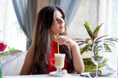 Woman in   restaurant is drinking cocktail — Stock Photo
