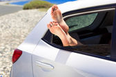 Womans legs dangling out a car window — Stock Photo