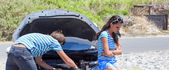 Man and woman near their broken car. — Stock Photo