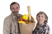 Retired couple with groceries — Stock Photo