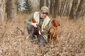 Hunter and his dog inthe forest — Stock Photo