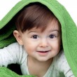 Happy baby covered with a green towel — Stock Photo