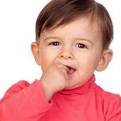 Schattige babymeisje met haar hand in mond — Stockfoto