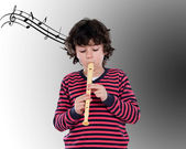 Adorable child playing flute — Stockfoto