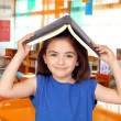 Brunette little girl with a book on her head — Stock Photo #19229713