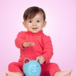 Adorable baby girl sitting with a blue piggy-bank — Stock Photo