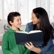 Mother teaching her child to read - Foto Stock