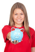 Teenager girl with a moneybox (with focus on the piggybank) — Stock Photo