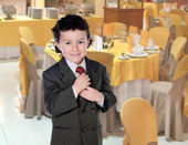 Elegant little boy clutching his tie in a restaurant — Stock Photo