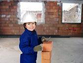 Happy little boy bricklayer — Stock Photo