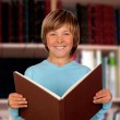 Preteen boy with a big book reading — Stock Photo