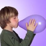 Adorable preteen boy blowing up a purple balloon — Stock Photo