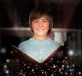Preteen boy with a lighted book reading — Stock Photo
