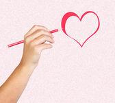 La main avec un crayon rouge, peindre un coeur — Photo