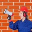 Industrial worker woman with a megaphone - Stock Photo